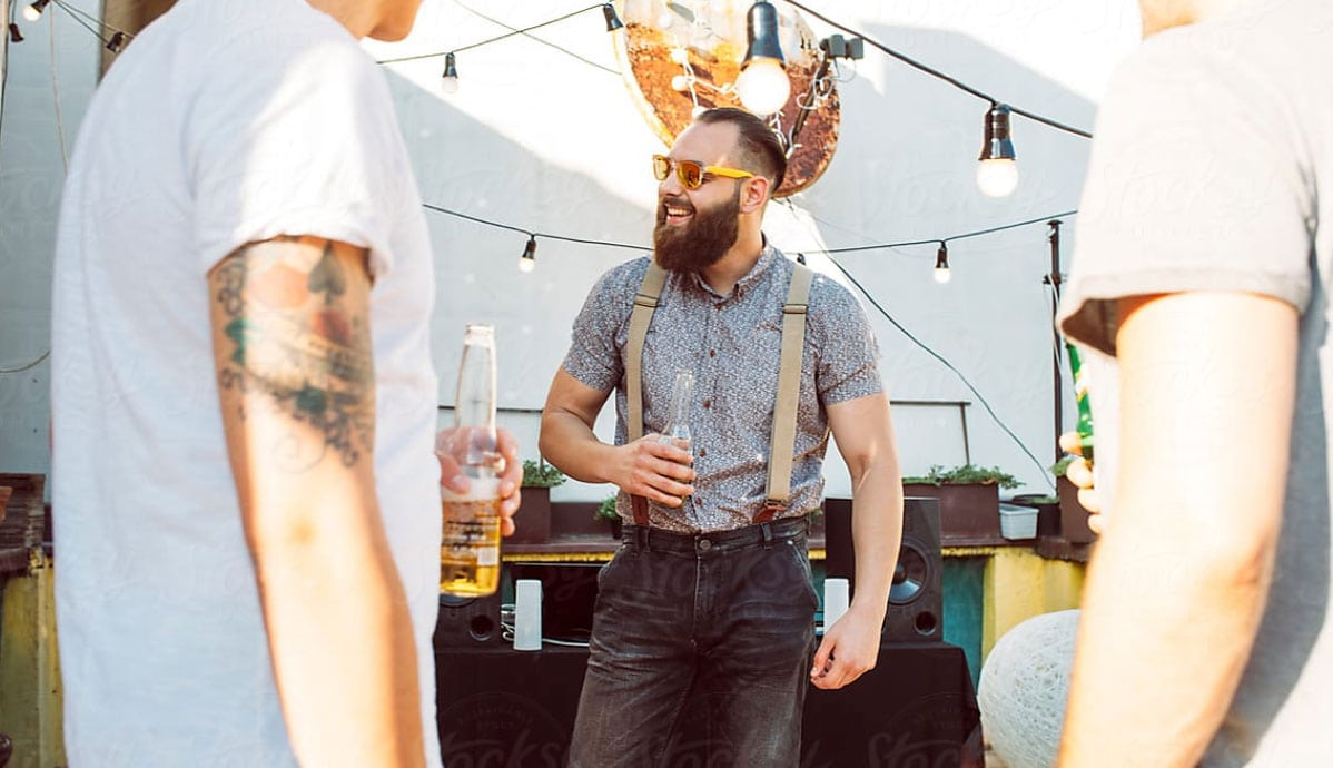 A young man with a beard and a beer in his hand enjoys time with his friends by a DJ table