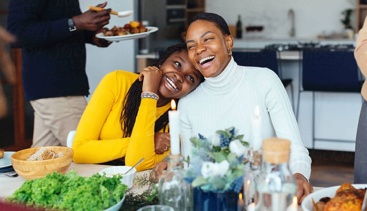 2 African American women share a laugh while sitting together at a restaurant